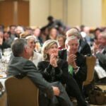 Senator Kay Bailey Hutchison and others seated at a table applaud a presenter at the 2015 KBH Symposium