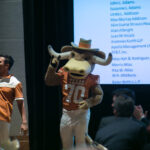 A student and a student in a Bevo costume give the Longhorns hand sign